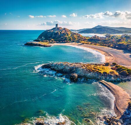 View from flying drone. Captivating summer view of popular tourist destination - Acropoli di Bithia with Torre di Chia tower on background. Stunning morning view of Sardinia island, Italy, Europe. Archivio Fotografico
