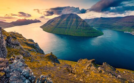 Astonishing sunset view from populat tourist attraction - Klakkur peak, Faroe Islands, Denmark, Europe. Colorful evening scene of Kalsoy island. Beauty of nature concept background.