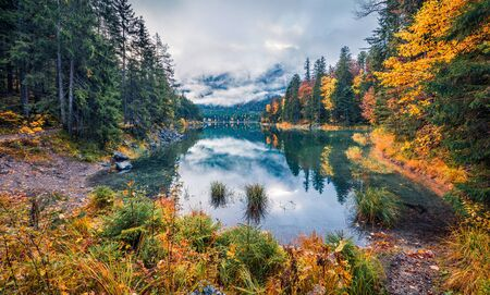 Gloomy morning view of Eibsee lake. Amazing autumn scene of Bavarian Alps, Germany, Europe. Foggy mountain hills reflected in the calm surface of water ot pure lake. Beauty of nature concept background. Stock Photo