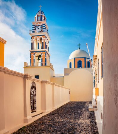 Perfect morning view of Catholic Cathedral Church of Saint John The Baptistm in Fira village, Greece, Europe. Sunny summer Santorini island. Traveling concept background.