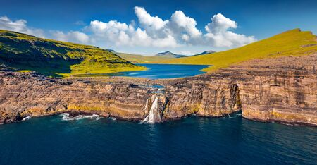 View from flying drone. Panoramic morning view of Bosdalafossur waterfall, that falls directly into the ocean. Exciting summer scene of Sorvagsvatn lake, Vagar, Faroe Islands, Denmark, Europe.