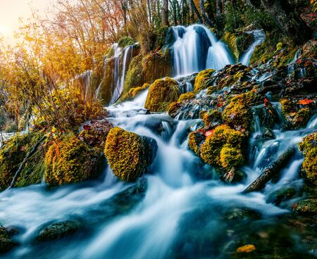 Sunny morning view of pure water waterfall in Plitvice National Park. Fantastic sunrise on autumn forest in Croatia, Europe. Beauty of nature concept background.