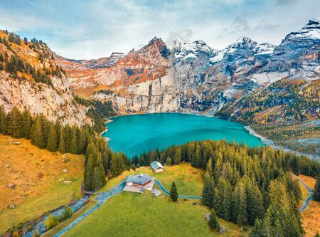 View from flying drone. Stunning autumn view of unique Oeschinensee Lake. Great morning scene of Swiss Alps with Bluemlisalp mountain on background, Switzerland, Europe.