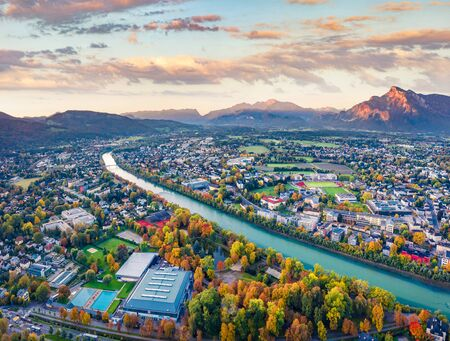 View from flying drone. Magnificent morning cityscape of Salzburg, Old City. Fantastic autumn sunrise on Eastern Alps. Aerial landscape with Salzach river. Traveling concept background.