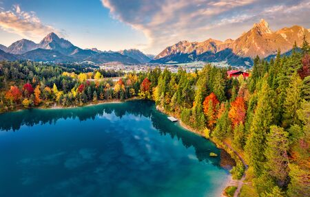 View from flying drone. Majestic morning scene of Urisee lake. Fabulous autumn view of Reutte town, Austria, Europe. Fantastic sunrise in Austrian Alps. Traveling concept background. Reklamní fotografie