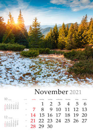 Calendar November 2021, vertical B3 size. Set of calendars with amazing landscapes. First snow in mountain forest. Bright morning scene of Carpathian mountains, Ukraine, Europe.
