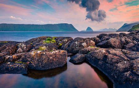 Calm morning waters of Atlantic ocean in fjord of Hestur Island. Fantastic sunrise on outskirts of Kirkjubour village, Faroe Islands, Denmark, Europe. Beauty of nature concept background.