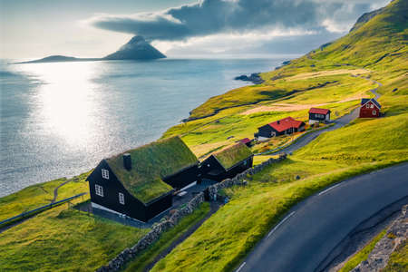 View from flying drone. Captivating summer view of Velbastadur village with typical turf-top houses. Incredible evening scene of Streymoy island, Faroe, Denmark, Europe.
