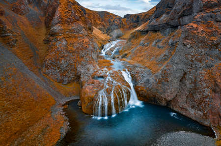 View from flying drone of Stjornarfoss waterfall at midnight sun. Splendi autumn scene of Iceland, Europe. Beauty of nature concept background. Travel to Iceland.