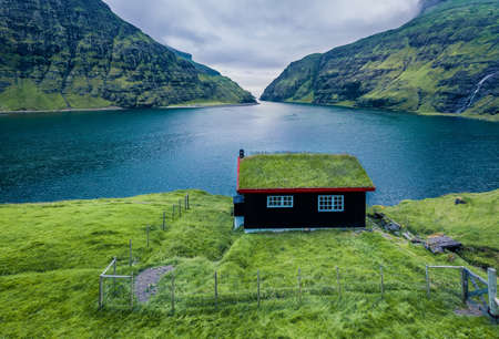 Stunning summer view of Saksun village with traditional turf-top house. Wonderful morning scene of Pollurin Laguna, Faroe Islands, Denmark, Europe. Traveling concept background.
