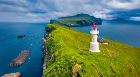 Gloomy view from flying drone of Mykines island with old lighthouse. Attractive morning scene of Faroe Islands, Denmark, Europe. Dramatic seascape of Atlantic ocean. Traveling concept background.