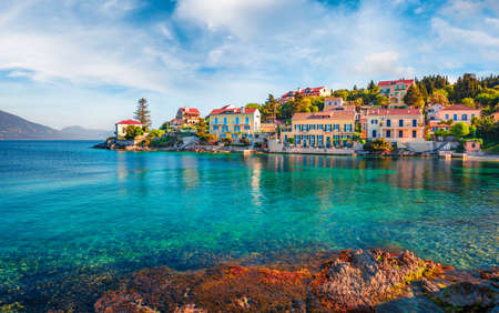 Exciting spring cityscape of Fiskardo town with Zavalata Beach. Romantic morning seascape of Ionian Sea. Wonderful outdoor scene of Kefalonia island, Greece, Europe. Traveling concept background. Stock Photo