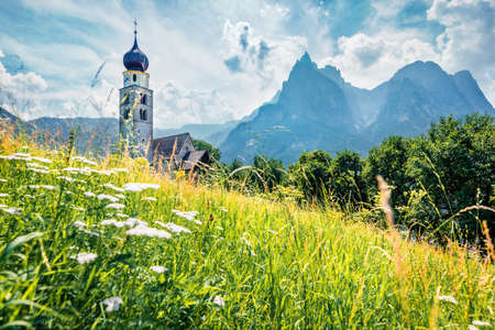 Stunning morning view of San Valentino Church in Castelrotto / Kastelruth village. Bright summer scene of Dolomiti Alps, South Tyrol, Italy. Europe. Traveling concept background.