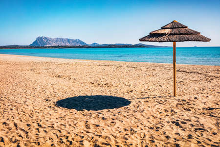 Sunny spring view of empty La Cinta beach with Tavolara island on background. Picturesqaue morning scene of Sardinia island, Italy, Europe. Attractive Mediterranean seascape. Imagens
