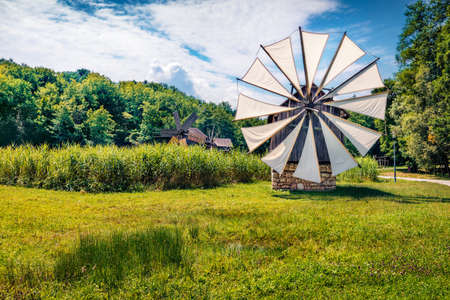 Spectacular summer view of traditional romanian windmill. Perfect rural scene of Transylvania, Romania, Europe. Beauty of countryside concept background.