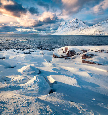 Dramatic winter view of Lofoten Islands, Norway, Europe. Snowy morning scene of popular tourist destination - Skagsanden beach, Flakstadoya island. Untouched Winter Landscape.