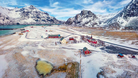 View from flying drone of Flakstad village with Hustinden mount on background, Norway, Europe. Breathtaking spring scene of Lofoten Islands. Impressive morning landscape with Flakstad church.