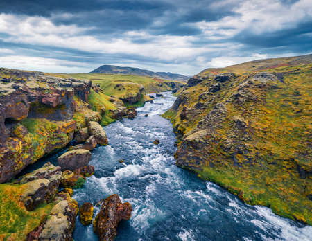 View from flying drone of Skoga river. Aerial summer landscape taken from the tourist trek from famous Skogafoss waterfall to the top of the river, Iceland, Europe.