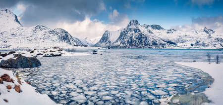 Incredible winter scene over polar circle. Frozen Boosen fjord on Flakstadoya island. Panoramic morning view of Lofoten islands with Hustinden mountain on background, Norway, Europe.