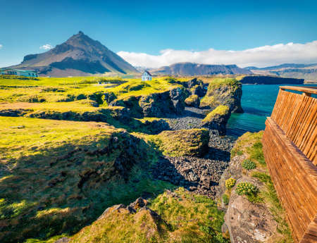 Superb summer view of small fishing village at the foot of Mt. Stapafell - Arnarstapi or Stapi. Bright morning scene of Icelandic countryside. Traveling concept background.