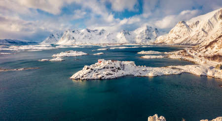 View from flying drone of Sandvika bay, Leknes, Norway, Europe. Frosty morning scene of Lofoten Islands with lonely red house. Untouched winter landscape. Beauty of nature concept background.