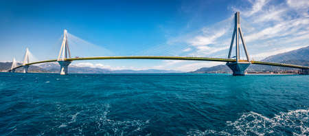 Panoramic morning view of Rion-Antirion Bridge. Colorful spring scene of Gulf of Corinth, Greece, Europe. Amazing Mediterranean seascape. Traveling concept background.