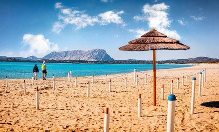 Sunny spring view of La Cinta beach with Tavolara island on background. Tourists walks on the shore of Mediterranean sea. Picturesqaue morning scene of Sardinia island, Italy, Europe. Imagens