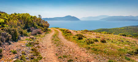 Colorful morning panorama of Ionian islands with old country road. Splendid spring view of Lefcada island, Greece, Europe. Amazing seascape of Ionia Sea. Beauty of nature concept background.