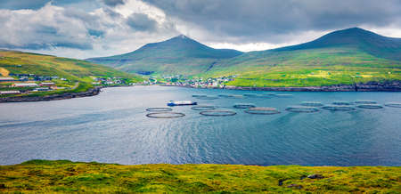 Panoramic summer view of Sandavagur village, Faroe Islands, Kingdom of Denmark, Europe. Gloomy morning view of fish farm on Vagar island. Traveling concept background. 免版税图像