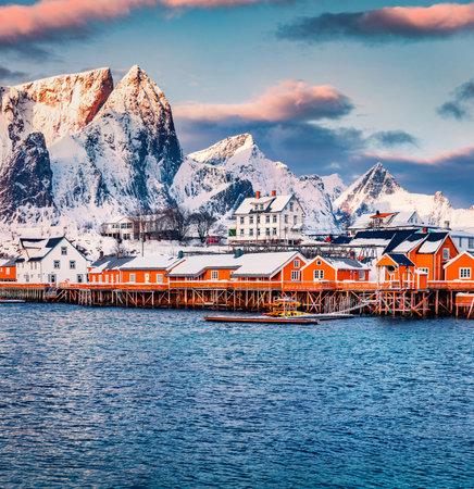 Fantastic winter sunrise on Gravdal bay. Colorful morning scene of popular tourist destination - Lofoten Islands. Beautiful seascape of Norwegian sea. Frosty winter landscape of Sakrisoy village.