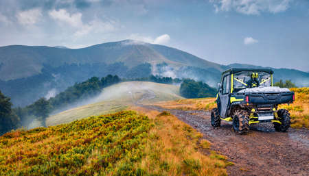 Traveling by all-terrain vehicle on the mountains. Off-road tour in Carpathian mountains, Ukraine, Europe. Foggy summer view of Krasna range. Traveling concept background.