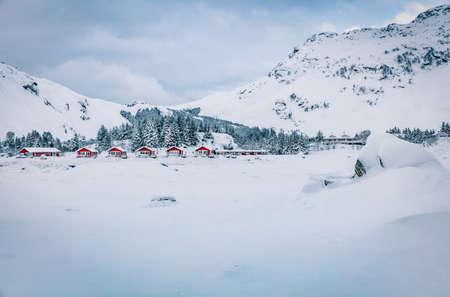 Traditional Norwegian red wooden houses under the fresh snow. Stunning winter scene of Lofoten islands on the shore of Kongsjordpollen fjord, Vestvagoy, Norway, Europe.Traveling concept background.