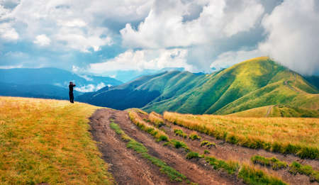 Tourist takes picture of mountain range with old country road. Gloomy summer view Svydovets range, Carpathian mountains, Ukraine, Europe. Traveling concept background. 免版税图像