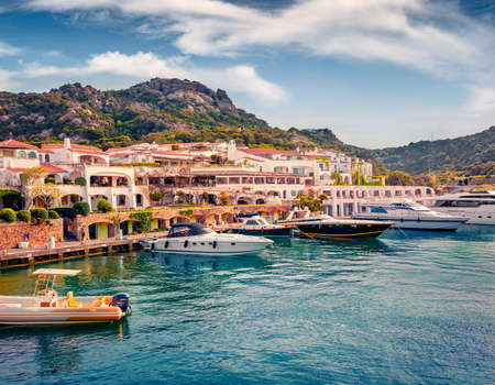 Adorable summer view of Poltu Quatu port with luxury yacht and motorboat. Stunning morning scene of Sardinia island, Italy, Europe. Bright Mediterranean seascape. Traveling concept background.