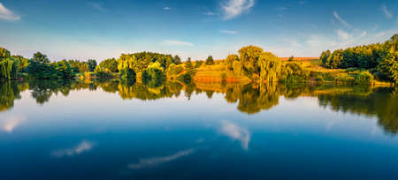 Calm morning scene of small pond in the outskirts of Ternopil town, West Ukraine, Europe. Panoramic summer view of Ukrainian countryside. Beauty of nature concept background. 免版税图像
