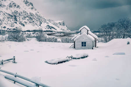 Dramatic morning scene after huge snowfall over polar circle. Snowy winter scene of Lofoten Islands. Small cemetery on Vestvagoy island, Norway, Europe. Vintage filtered.