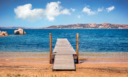 Old wooden pier on public beach of Rafael port, Province of Olbia-Tempio, Italy, Europe. Bright morning view of Sardinia. Colorful seascape om Mediterranean sea. Traveling concept background. 免版税图像