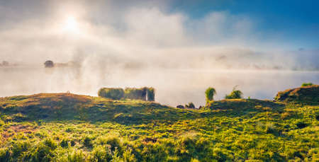 First sunlights illuminated through a thick fog. Panoramic summer view of small pond on the outskirts of ternopil town, Ukraine, Europe. Beauty of nature concept background.