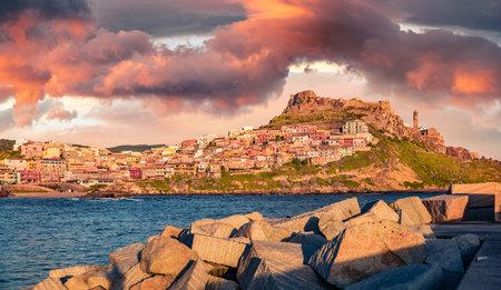 Panoramic morning cityscape of Castelsardo port. Amazing sunrise on Sardinia island, Province of Sassari, Italy, Europe. Colorful summer seascape of Mediterranean sea. Traveling concept background. 免版税图像