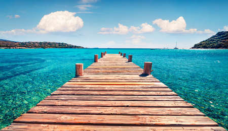 Splendid summer scene with wooden pier of Santa Giulia beach. Stunning morning scene of Corsica island, France, Europe. Bright Mediterranean seascape. Pure water Mediterranean resort.