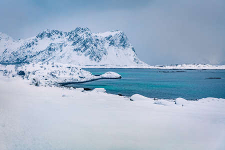 Calm winter scene of Vestvagoy island. Snowy mountain peak on Lofoten Islands, after huge snowfall. Picturesque seascape of Norwegian sea. Beauty of nature concept background. 免版税图像
