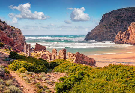 Ruines of old villageon Cala Domestica beach. Sunny summer scene of Sardinia, Italy, Europe. Picturesque landscape of Canyon di Cala Domestica. Beauty of nature concept background.