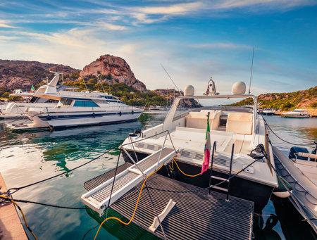 Loxuary yachts ant motor boards on Poltu Quatu port. Sunny morning scene of Sardinia island, Italy, Europe. Splendid Mediterranean seascape. Traveling concept background.