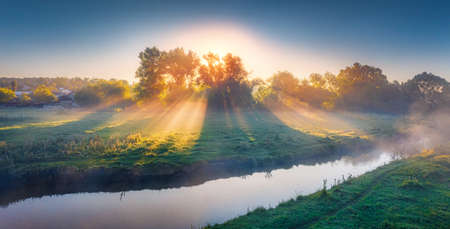 Fantastic summer sunrise on the misty river. Panoramic morning scene with first sunlight glowing foggy valley, Ternopil region, Ukraine, Europe. Beauty of countryside concept background. 免版税图像