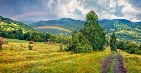 Double rainbow at the summer rain. Gorgeous evening view of Kvasy village, Transcarpathian, Ukraine. Picturesque landscape of Carpathian mountains. Beauty of countryside concept background.