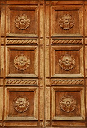 A decorative carved wooden door in Florence, Tuscany, Italy