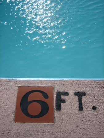 depth measurement: A swimming pool-side depth indicator, with water glinting in the sun  Stock Photo