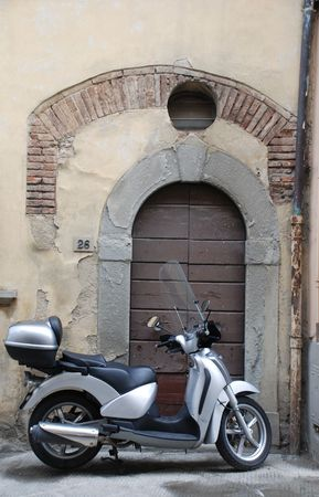 which: A shiney new motorbike contrasts with the old Tuscan building which its parked outside