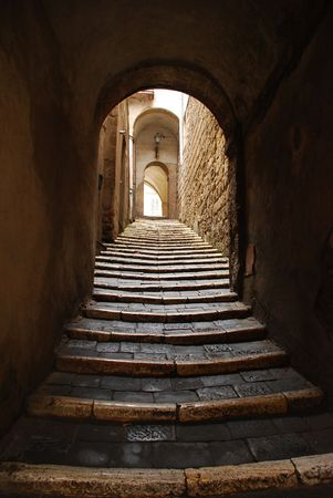 A steep pedestrian street with steps along it in the historic Tuscan town of Pitigliano, Italy  photo