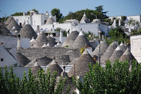 which: A panaroma of the trulli in Alberobello in Puglia, southern Italy. The trulli, which are protected under UNESCO World Heritage laws, are traditional limestone houses with domed or conical roofs, and are common in the Alberobello region  Stock Photo